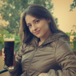 Smiling happy woman drinking dark beer on terrace cafe. Closeup — Stok fotoğraf