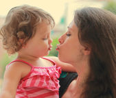 Beautiful young mother and baby girl going to kiss on nature bac — Stock Photo