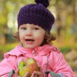 Funny kid girl eating apple on bright autumn background — Stock Photo