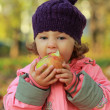 Happy child eating big red apple on autumn bright background — Stock Photo