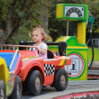 Driving car baby girl on road in amusement park on weekend — Stock Photo
