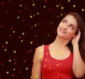 Krásná usměvavá žena myslet na červené vánoční pozadí — Stock fotografie