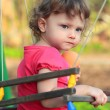 Cute child girl swinging and looking serious on summer backgroun — 图库照片