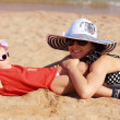Happy mother and kid lying on the sand on beach in hat and glasses — Stock Photo