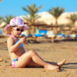 Stock Photo: Sunbathing kid girl in hat sitting on sand and looking
