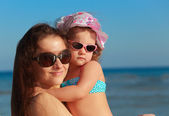 Beautiful happy mother and kid girl on blue sea background — Stock Photo