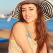Foto Stock: Happy smiling womin hat on sebackground. Closeup portrait