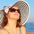 Beautiful woman in hat and sun glasses looking up and joy on blue sea background — Stock Photo #39778593