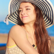 Foto Stock: Beautiful womin hat joying sunny summer day and looking on sebackground
