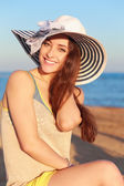 Beautiful smiling woman in hat on beach background — Stock Photo