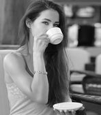 Beautiful thinking girl drinking coffee in cafe. Black and white portrait — Stock Photo