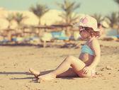 Söt liten flicka med att sola på stranden. Instagram effekt — Stockfoto
