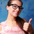 Happy girl in glasses showing thumb up sign on blue background — Stock Photo #42551365