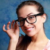 Beautiful woman in glasses looking happy on blue background — Stock Photo