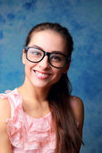 Happy smiling girl in glasses on blue background — Stock Photo