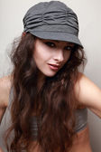 Beautiful smiling long hair trendy woman in cap. Hip-hop style — Stock Photo