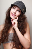 Thinking smiling teenager girl looking up in trendy cap. Closeup — Stock Photo