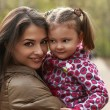 Beautiful mother and kid girl cuddling on green summer background. Closeup — Stock Photo