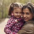 Beautiful happy mother and kid girl cuddling outdoors. Closeup portrait — Stock Photo