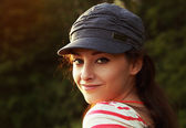 Beautiful woman in cap outdoors summer background — Stock Photo