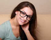 Happy woman in glasses on sofa at home looking — Stock Photo