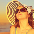 Beautiful woman in hat and sunglasses enjoying sunset on the beach. Bright orange portrait — Stock Photo #48176265