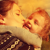 Bright closeup portrait of happy mother kissing laughing daughter. Instagram effect — Stock Photo