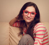 Happy girl sitting on sofa and looking in fashion red glasses. Vintage portrait — Stock Photo