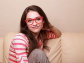 Beautiful smiling girl in red glasses sitting on sofa — Stock Photo