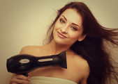 Happy smiling woman drying long hair and looking in camera. Instagram effect portrait — Stok fotoğraf