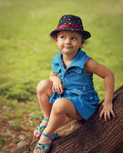 Cute fun kid girl in hat and fashion blue dress sitting on the tree in park — Stock Photo