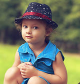 Fashion beautiful child girl in blue jeans dress sitting and looking happy. Closeup portrait — Stock Photo