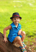 Funny fashion kid girl in blue bright dress sitting on tree on summer green background — Stock Photo