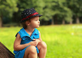 Cute fashion clothing kid girl sitting on tree on green summer background — Stock Photo