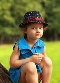 Cute kid in fashion hat sitting on green park summer background — Stock Photo