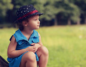 Fashion kid girl in hat sitting on green summer background — Stock Photo