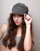 Sexy hip hop girl in trendy cap looking holding the cap — Stock Photo