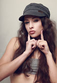 Hip-hop girl in hat posing and showing kissing sign holding fingers near lips — Stock Photo