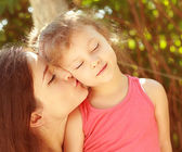 Enjoyment. Mother kissing happy kid with closed eyes outdoors summer background — Stock Photo