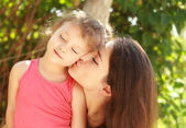 Happy young mother kissing her happy joying kid with love on summer background — Stock Photo