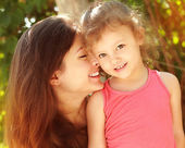 Loving family. Beautiful mother and happy smiling kid girl outdoors. Closeup portrait — Stock Photo