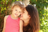 Happy loving mother and smiling kid girl outdoor summer background — Stock Photo
