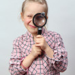 Girl explores with a magnifying glass. — Stock Photo