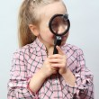 Stock Photo: Girl explores with a magnifying glass.