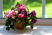Colorful roses in a basket on window-sill — Stock Photo