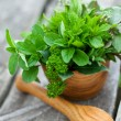 Fresh herbs in a wooden mortar — Stock Photo