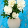 Stock Photo: White roses in vase on blue wooden background