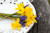 Narcissus and muscari flowers on wooden table — Stock Photo