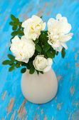 White roses in vase on blue wooden background — Stock Photo