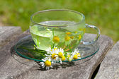 Chamomile tea on wooden background — Stock Photo